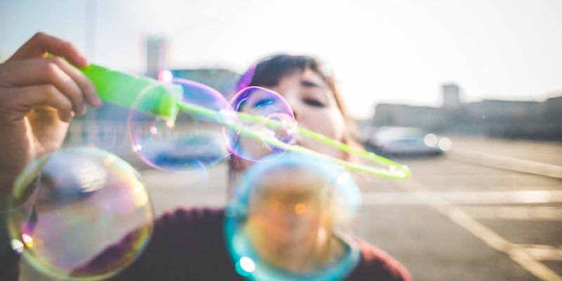Mile Two: Creativity. Image is a close-up of young lady wearing a warm-looking purple sweater blowing bubbles into the camera. She is standing on what appears to be the top of a parking garage, and even though it looks chilly outside, a lens flare in the background reveals that it is at least a sunny day.